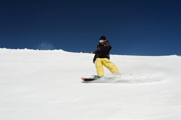 Lo snowboarder pattina nella neve contro il cielo blu