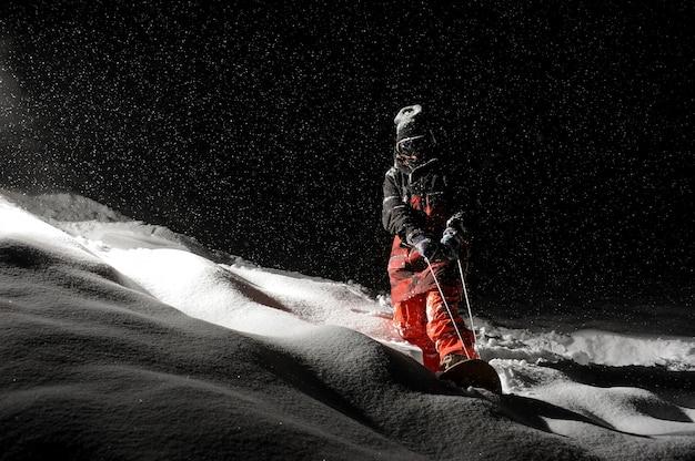 Lo snowboarder si è vestito nell'abbigliamento sportivo arancione che guida sul bordo