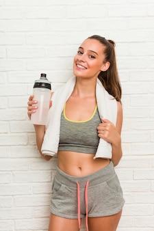 Lo sport da portare della giovane donna caucasica copre con una bottiglia di acqua