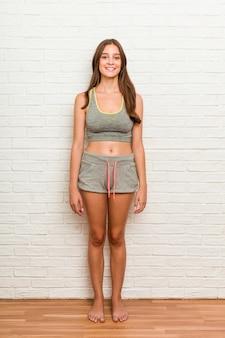 Lo sport da portare della giovane donna caucasica copre contro il muro di mattoni
