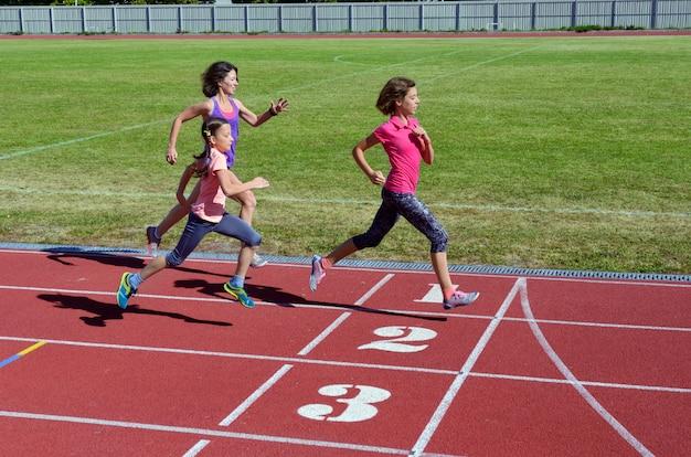 Lo sport e la forma fisica della famiglia, la madre felice ed i bambini che corrono sullo stadio seguono all'aperto, concetto attivo sano di stile di vita dei bambini