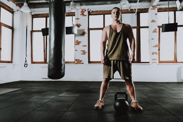 Lo sportivo caucasico sta esercitandosi in palestra da solo