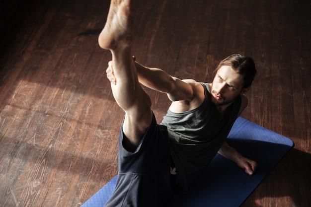 Lo sportivo forte bello in palestra fa gli esercizi di sport di yoga