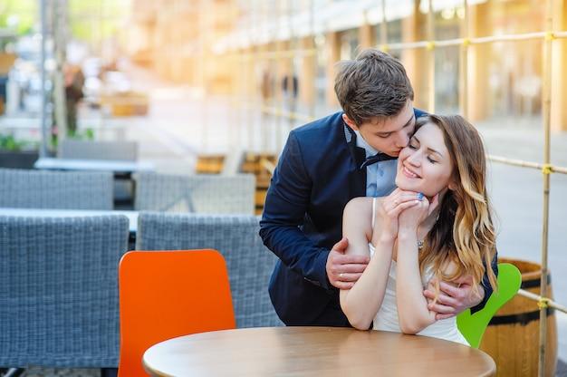 Lo sposo abbraccia le spalle della sposa a un tavolo in un caffè