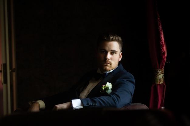 Lo sposo alla moda aspetta la sposa vicino alla finestra. ritratto dello sposo in un abito nero