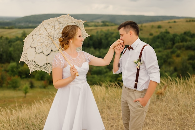 Lo sposo bacia la mano della sposa contro uno splendido paesaggio