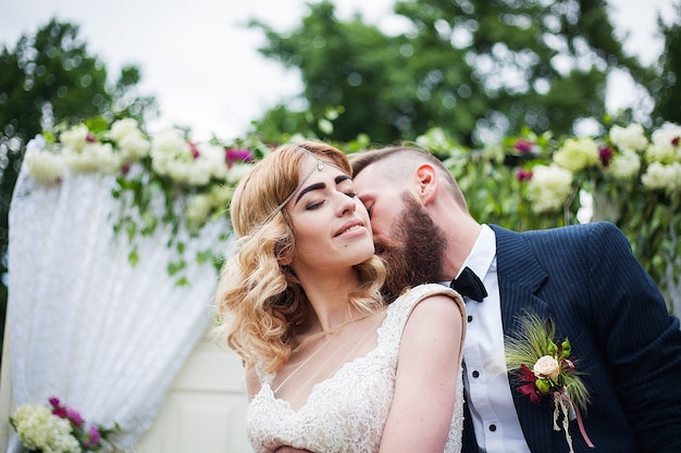 Lo sposo bacia la sposa su un arco floreale in natura, stile rustico