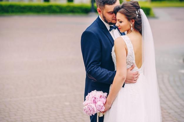 Lo sposo barbuto abbraccia delicatamente la sua bellissima sposa