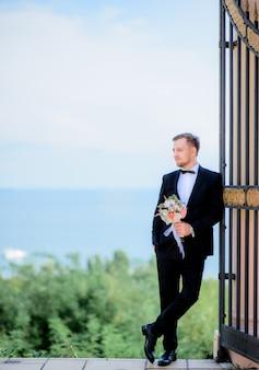 Lo sposo bello si appoggia alle porte in piedi davanti a una splendida vista sul mare