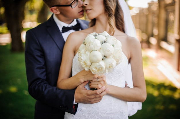 Lo sposo con gli occhiali sta per baciare la sposa affascinante in un abito bianco