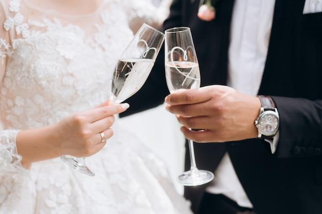 Lo sposo con la sposa bussa agli occhiali con lo champagne