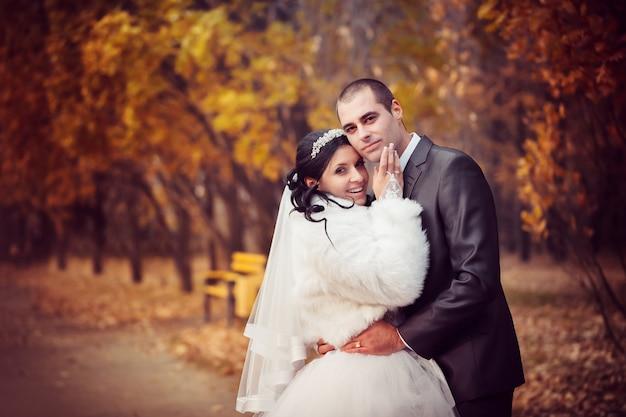 Lo sposo e la sposa nel parco d'autunno camminano vicino agli alberi con foglie gialle