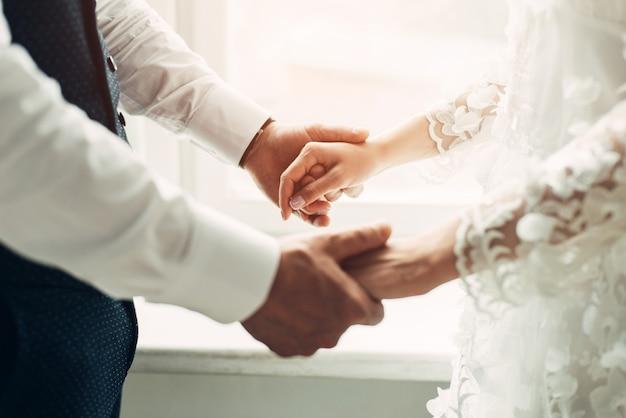 Lo sposo e la sposa si tengono per mano, primo piano