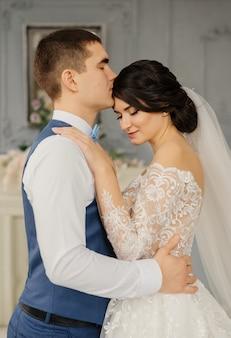 Lo sposo felice bacia la sposa che abbraccia la sua vita in un interno vintage. bella coppia elegante di sposi innamorati. concetto di matrimonio. coppia di sposi felici.