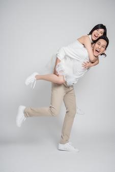 Lo sposo felice dà una sposa sulle spalle