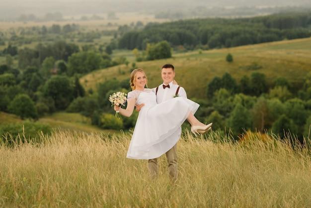 Lo sposo felice tiene tra le sue braccia la sua bella sposa, contro il bellissimo paesaggio.