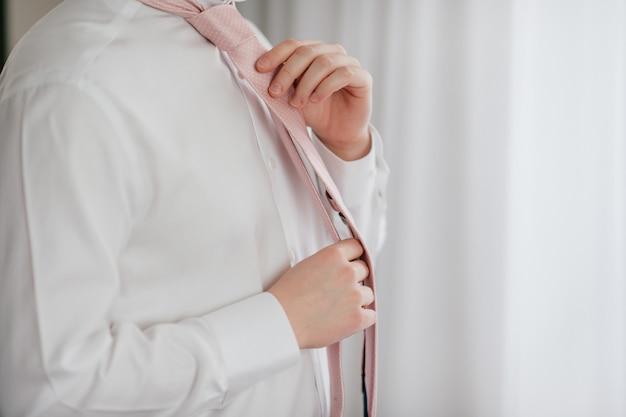 Lo sposo giovane sta preparando. fidanzata mattina a casa. sposo che fissa la cravatta.