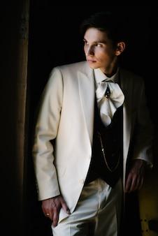 Lo sposo in abito bianco si pone al chiuso