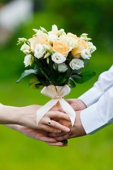Lo sposo in abito e la sposa in abito con mazzi di fiori
