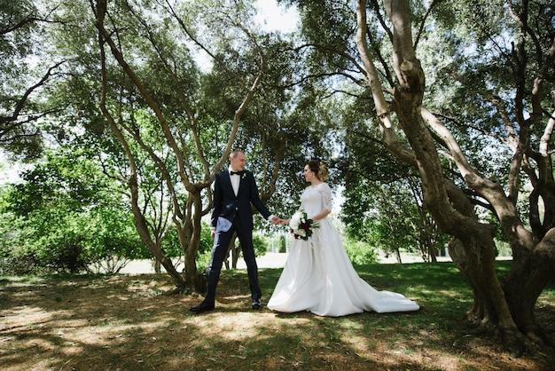 Lo sposo in abito e la sposa in abito da sposa stanno camminando nel parco