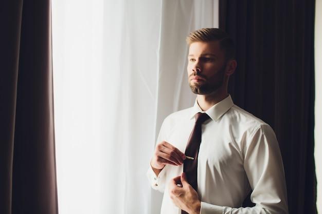 Lo sposo in una giacca, lo sposo si allaccia la giacca, la mattina dello sposo, le tasse dello sposo.