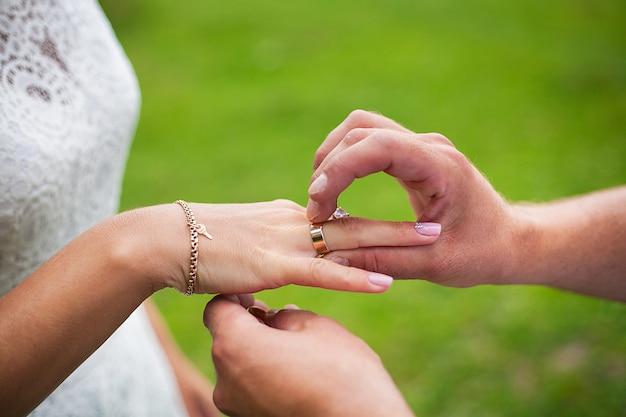 Lo sposo indossa l'anello sulla mano della sposa