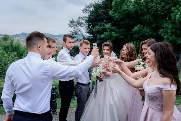 Lo sposo, la sposa, i migliori uomini e le damigelle stanno bevendo champagne all'aperto il giorno del matrimonio