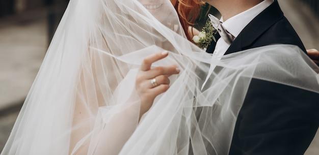Lo sposo porta affascinate la sposa sulle sue braccia