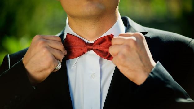 Lo sposo regola la sua farfalla