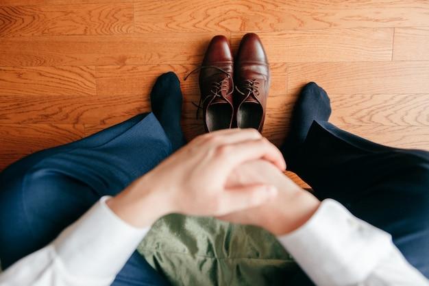 Lo sposo si prepara al mattino. mani, gambe e scarpe del primo piano dello sposo da sopra