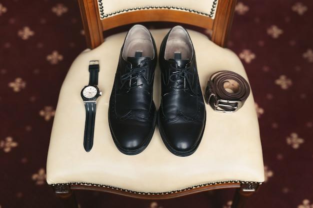 Lo sposo si sta radunando al mattino. scarpe classiche da uomo, cintura, toilette, profumo, cinturino in pelle, fedi nuziali.