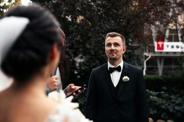 Lo sposo sorride all'aperto e vista posteriore della sposa