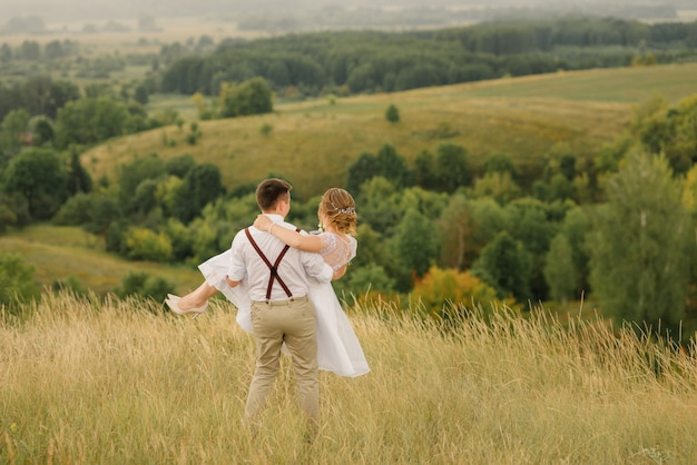 Lo sposo sta circondando tra le sue braccia una bellissima sposa, lo sposo felice tiene tra le sue braccia la sua bellissima sposa, contro uno splendido paesaggio. giorno del matrimonio.