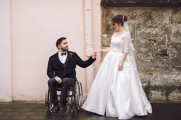 Lo sposo sulla sedia a rotelle tiene la mano della sposa in piedi davanti alla vecchia casa sulla strada