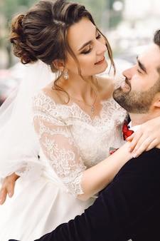 Lo sposo sulla sedia a rotelle tiene la sposa in ginocchio seduti fuori nel parco