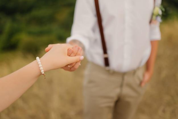 Lo sposo tiene la sposa per mano al matrimonio. avvicinamento.