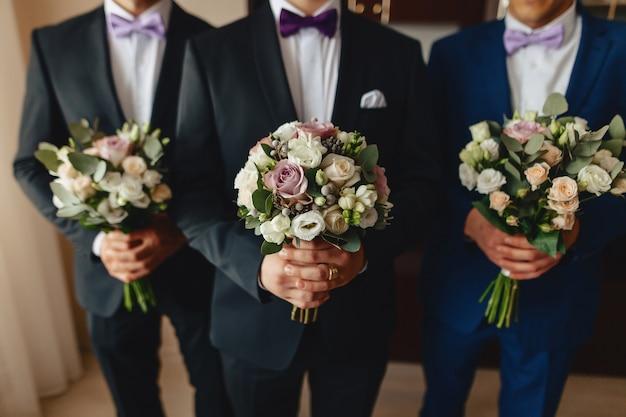 Lo sposo tiene un bouquet da sposa nelle sue mani