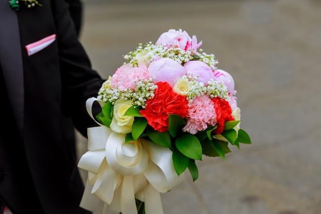 Lo sposo tiene un mazzo di fiori mani maschili