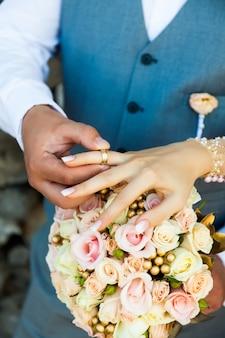 Lo sposo veste l'anello di fidanzamento della sposa al dito