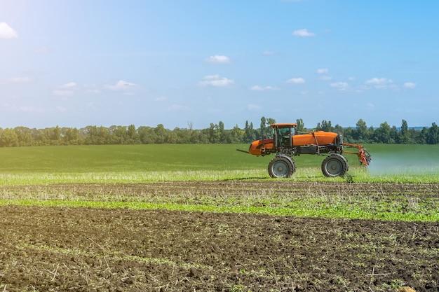 Lo spruzzatore automotore funziona su un campo sotto un cielo blu con le nuvole