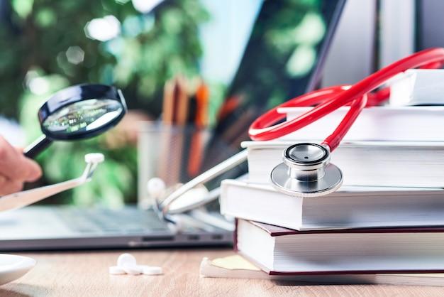 Lo stetoscopio giace su libri di medicina con una lente d'ingrandimento sopra una tavoletta con una pinzetta