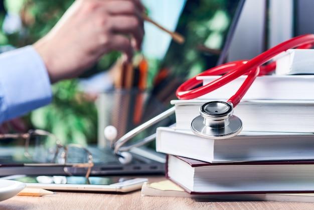 Lo stetoscopio giace su libri di medicina. la mano di un uomo tiene in mano una matita e la punta verso lo schermo del laptop