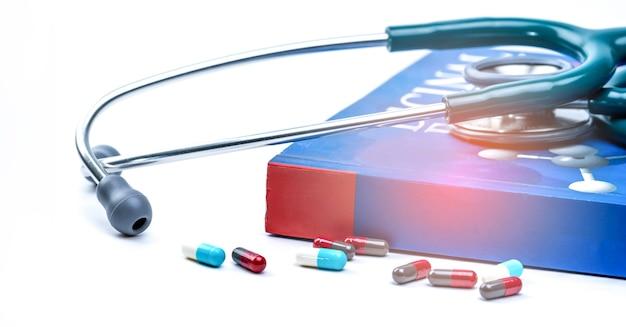 Lo stetoscopio ha messo sopra il manuale e le pillole sulla tavola bianca di medico