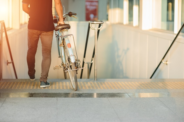 Lo stile di vita moderno delle persone urbane che usano le biciclette da portare va con la stazione della metropolitana della metropolitana in una giornata senza auto.