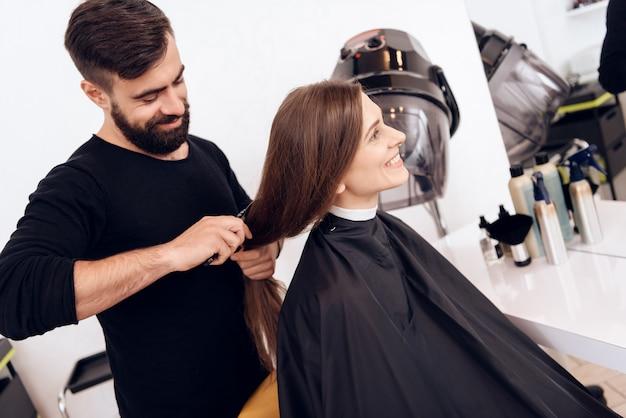 Lo stilista di parrucchiere sta pettinando la giovane donna con i capelli castani