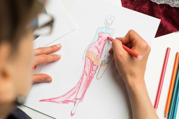 Lo stilista disegna uno schizzo di abbigliamento femminile.