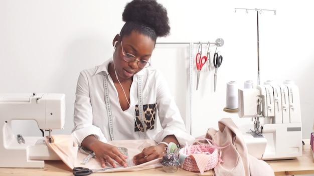 Lo stilista femminile afroamericano attraente cuce vestiti alla moda nel suo laboratorio