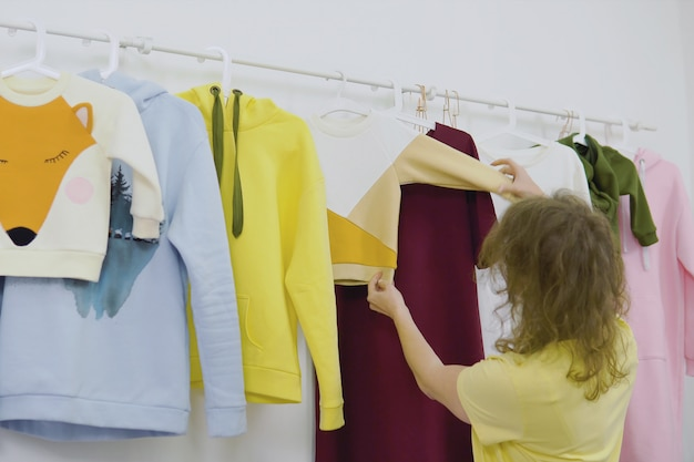 Lo stilista lavora alla nuova collezione di abbigliamento femminile in studio, sarta, sarta o sarta in piedi vicino al porta abiti