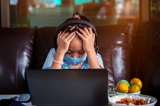 Lo stress bambina della scuola è studio a casa con il computer portatile e la maschera. concetto di formazione online