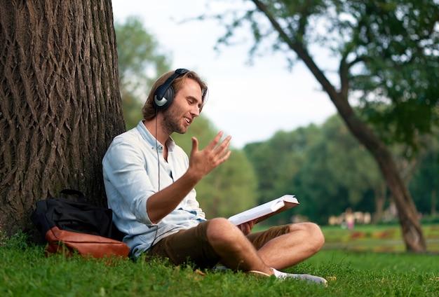 Lo studente allegro con le cuffie in parco della città universitaria ha letto un libro